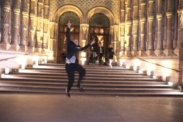 Gug jumping with excitement on the steps of the Natural History Museum in London